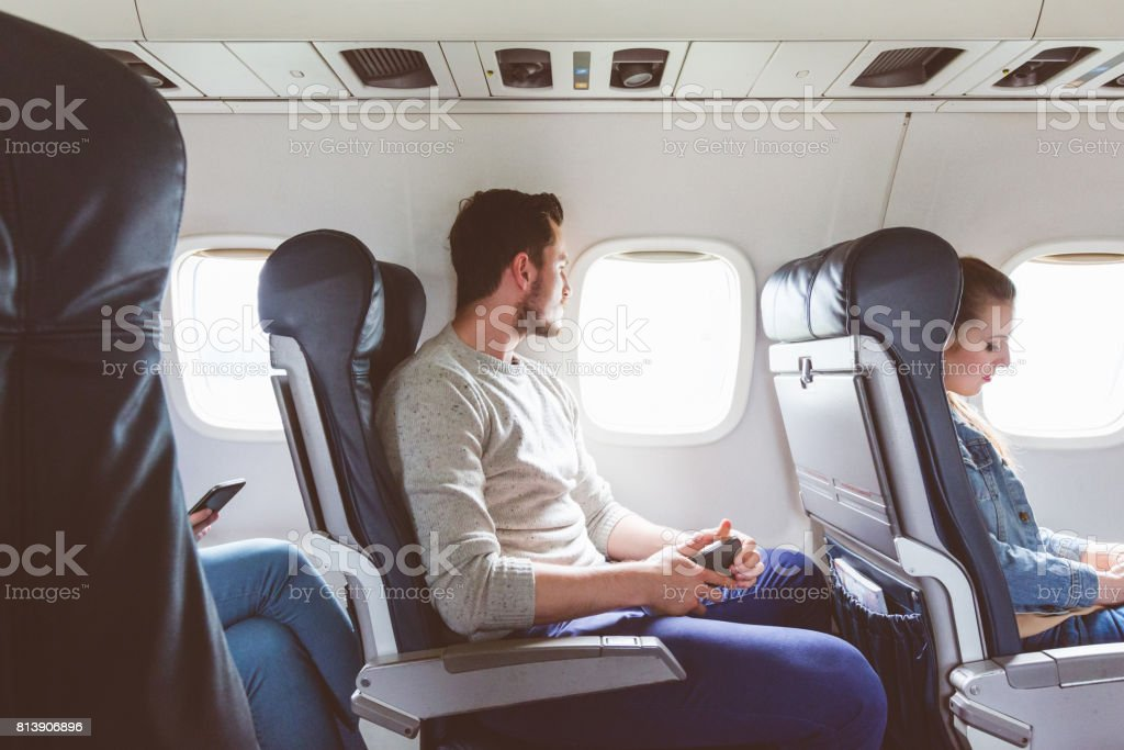 Young man sitting in airplane near window stock photo