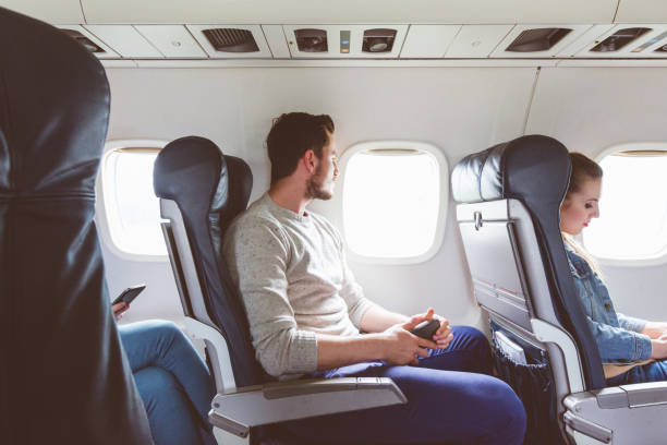 Young man sitting in airplane near window Young man sitting in airplane cabin near window. People flying by plane. passenger cabin stock pictures, royalty-free photos & images