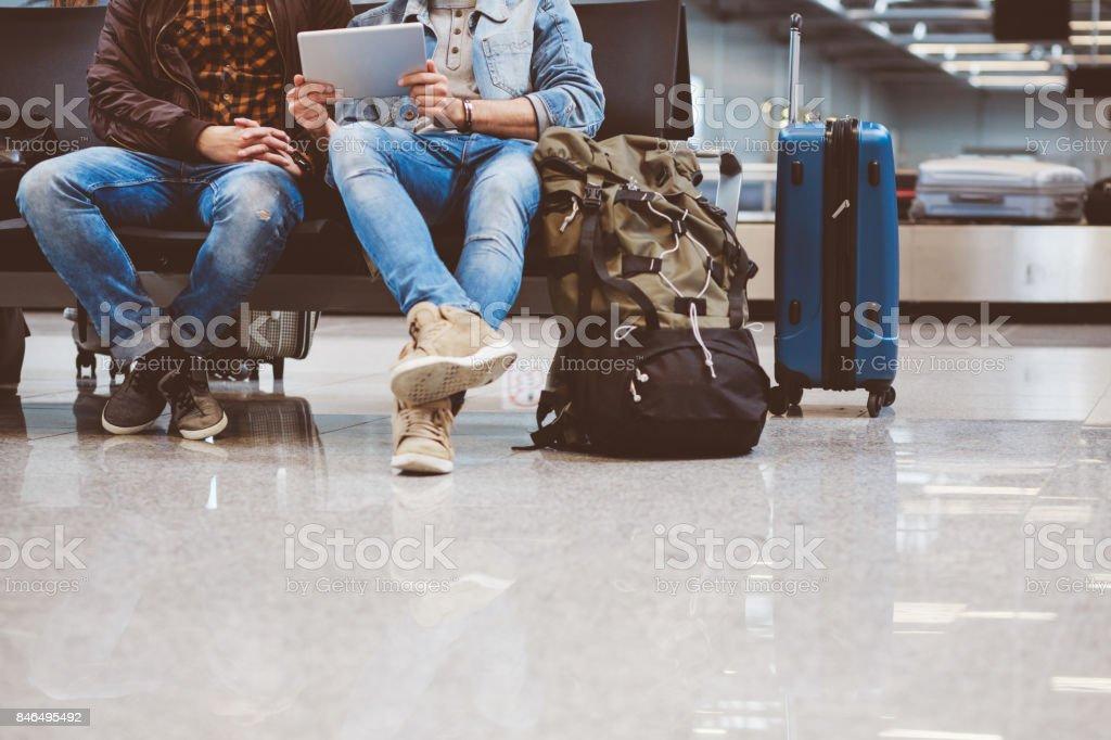 Junger Mann sitzt im Flughafen-Lounge mit digital-Tablette – Foto