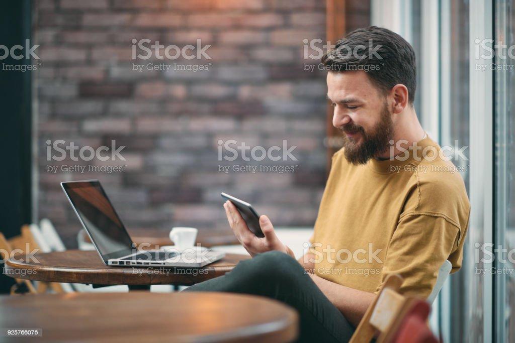 Joven sentado en la cafetería. - Foto de stock de Adulto libre de derechos