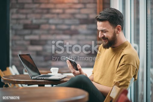 Young man sitting in cafeteria and using tablet computer