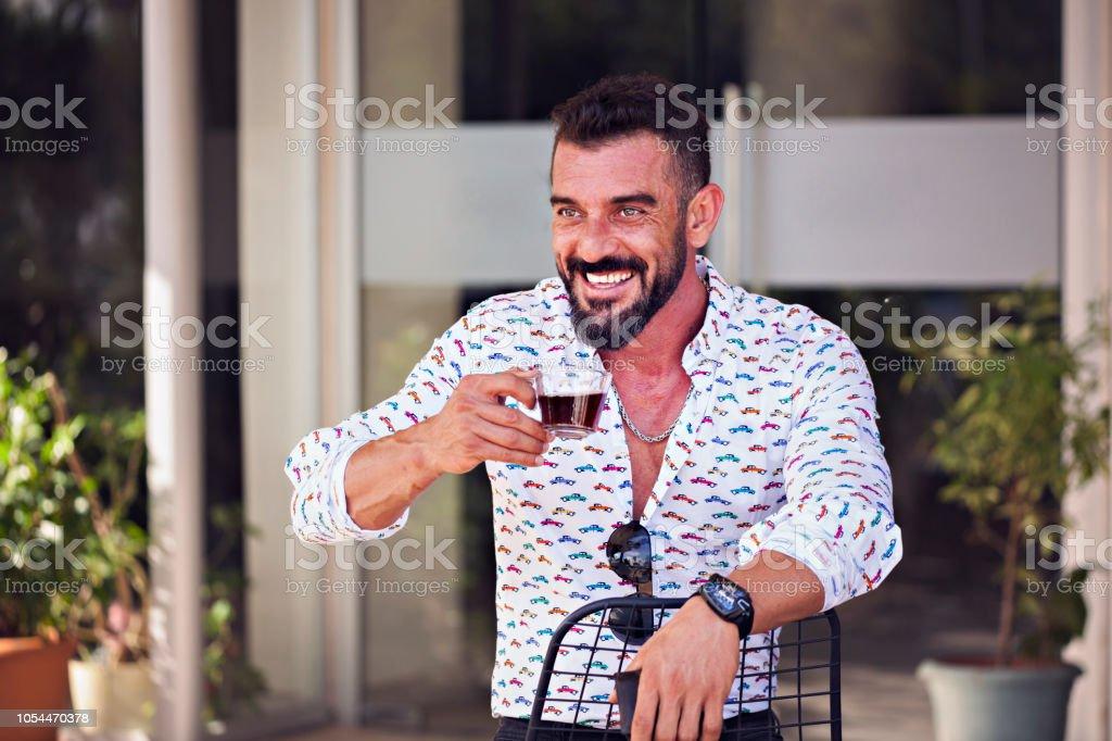 Kafede oturan ve Türk çay içme genç adam stok fotoğrafı