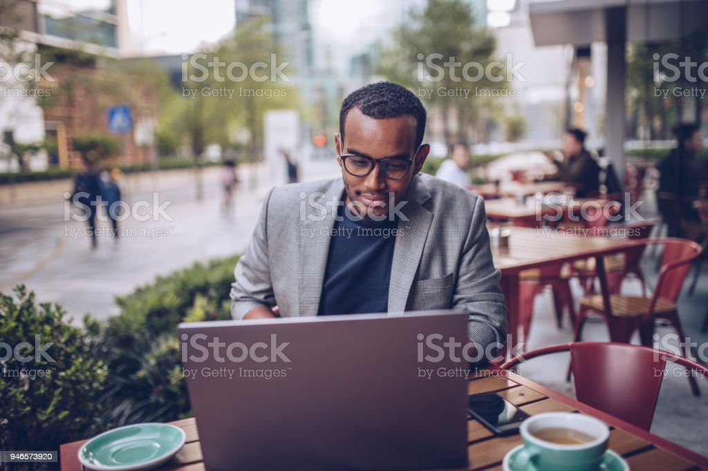 Young man sitting in coffee shop and using laptop stock photo