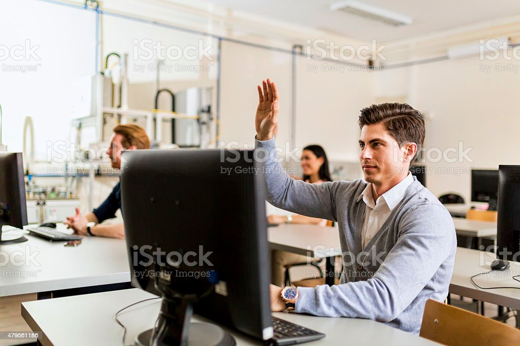 Young man sitting in front of a computer raising hand stock photo