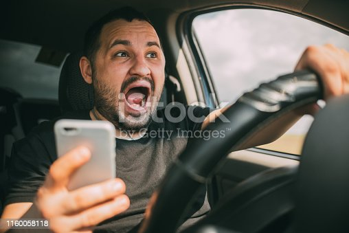 Young man sitting in his car screaming distracted by smartphone texting