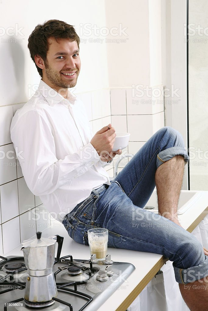 young man sitting in kitchen with breakfast royalty-free stock photo