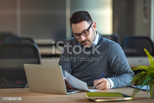 921587490 istock photo Young man sitting in office and working on laptop 1210848148