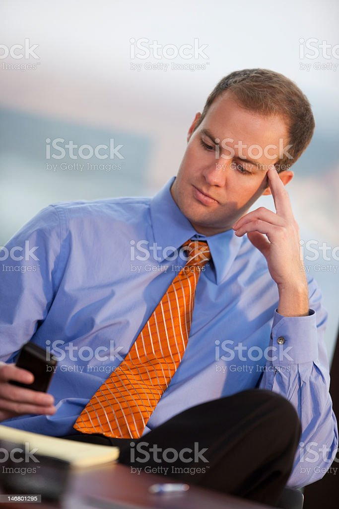 Young Man Sitting In Office Looking At Cellphone royalty-free stock photo