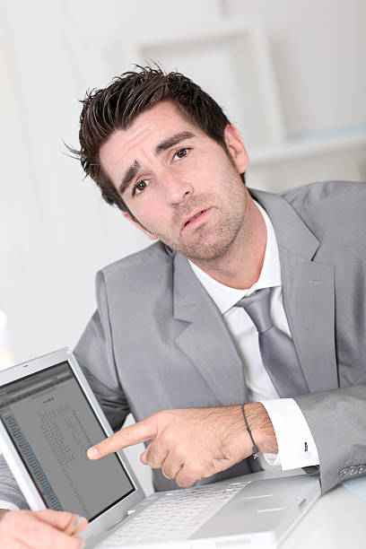 Young man sitting in office showing screen of digital tablet stock photo