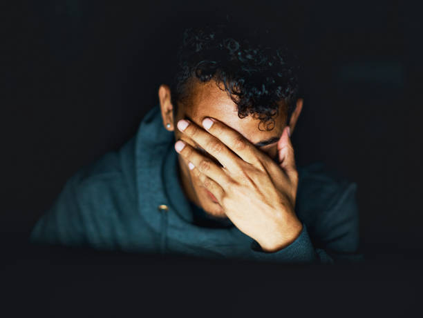 Young man sitting in the dark covers his face stock photo