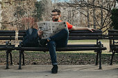 Young man sitting in the park and reading newspaper in Novi Sad serbia in sunny day and beautiful waether in spring time