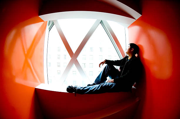 Young Man Sitting in Windowsill of Red Room stock photo