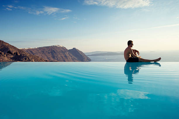 Young Man Sitting Infinity Pool Edge Caldera View Santorini Greece Man sits on the edge of an infinity pool gazing out at the misty Mediterranean seascape infinity pool stock pictures, royalty-free photos & images