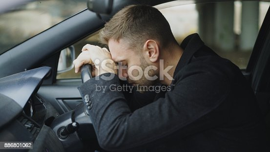 istock Young man sitting inside car is very upset and stressed 886801062