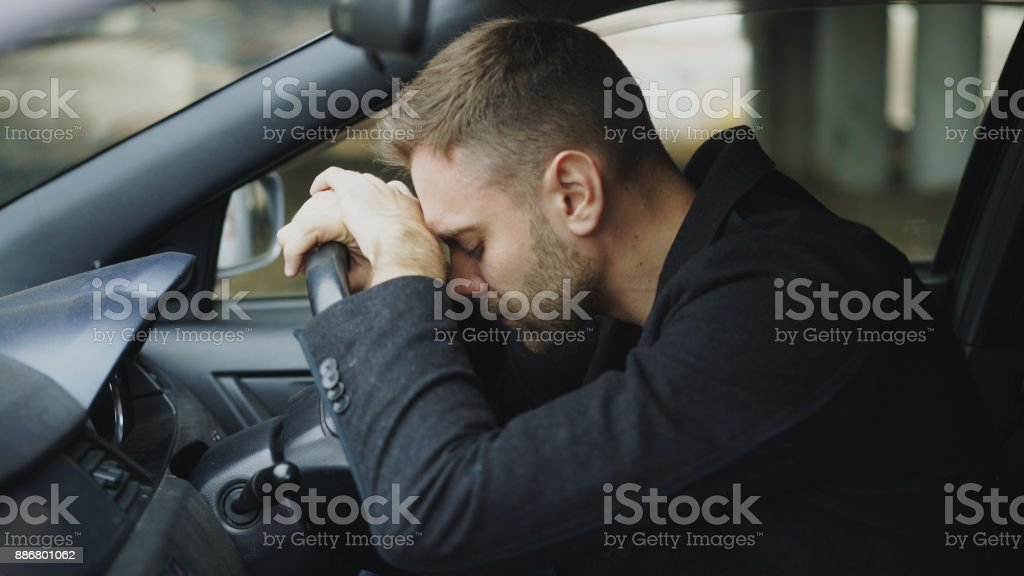 Young man sitting inside car is very upset and stressed stock photo