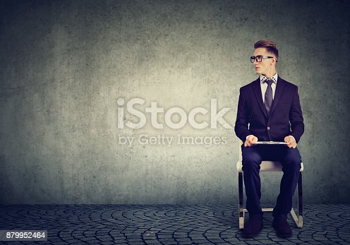 636681940istockphoto Young man sitting on a chair waiting for job interview 879952464