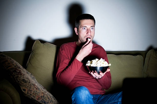 Young man sitting on a couch while watching TV and snacking stock photo