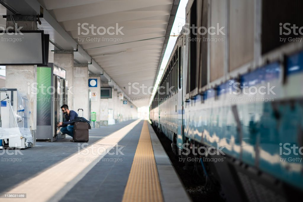 Young Man Sitting on a Railroad Station Platform by the Vending...