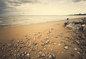 Young man sitting on a rock by the sea, on the beach of Sanlucar de Barrameda, Spain