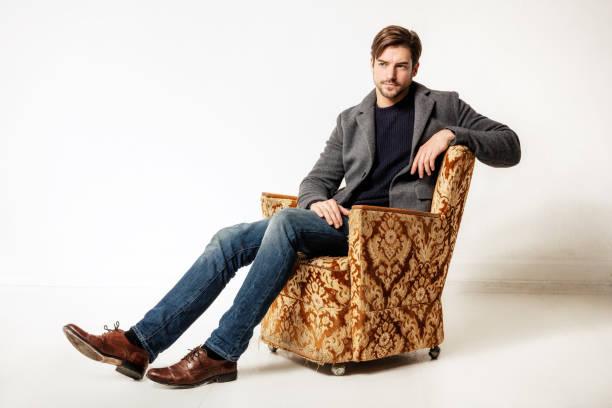 joven sentado en sillón - foto de stock