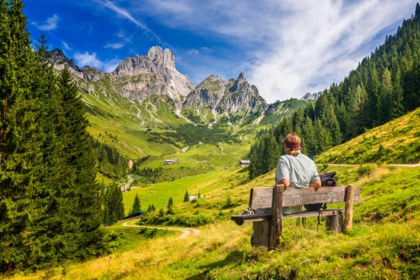 Junger Mann sitzt auf Der bank und genießt blickauf große Bischofsmütze, Dachsteingebirge, Alpen – Foto