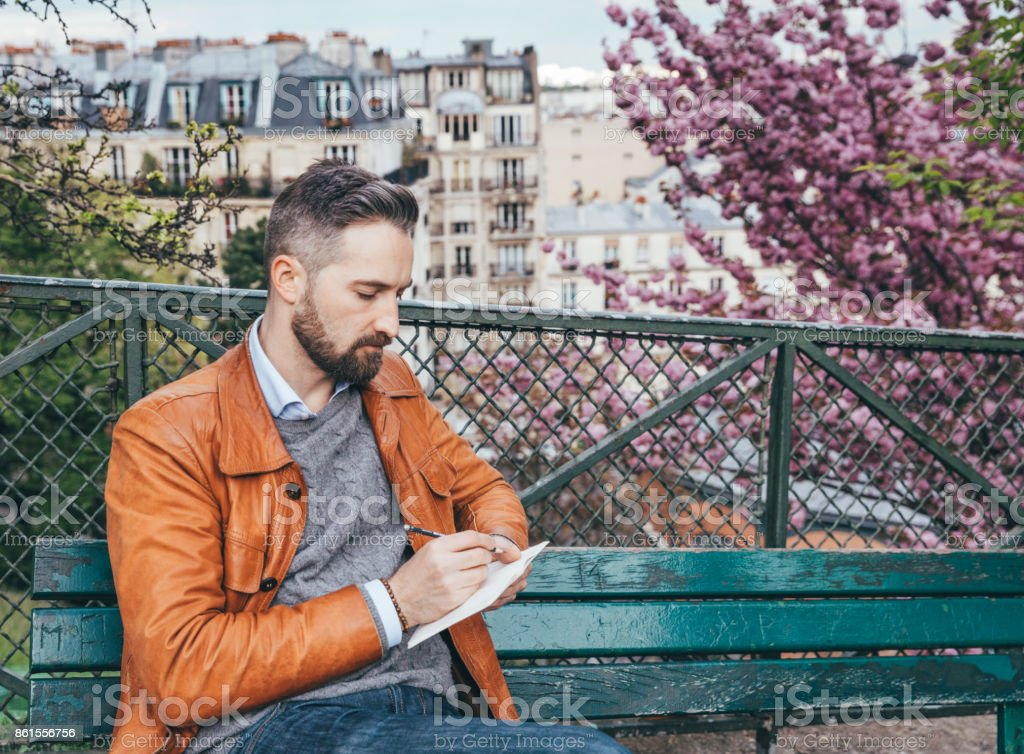 Young man sitting on bench with notebook, Montmartre, Paris stock photo