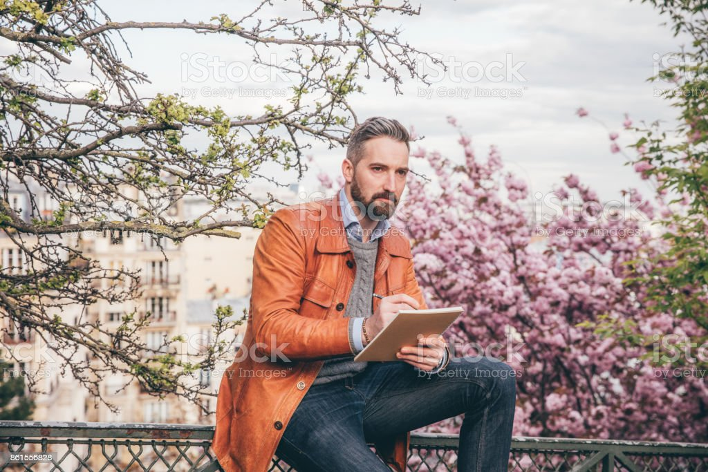 Young man sitting on bench with sketchbook, Montmartre, Paris stock photo