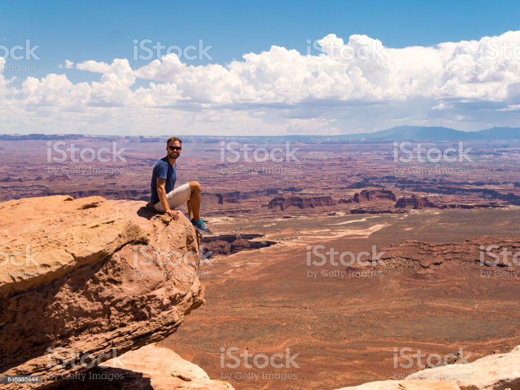 Young man sitting on cliff over canyonlands national park, moab, utah stock photo