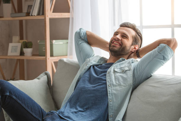 Young man sitting on coach rest at home Young male relaxing on sofa indoors carefree bachelor stock pictures, royalty-free photos & images