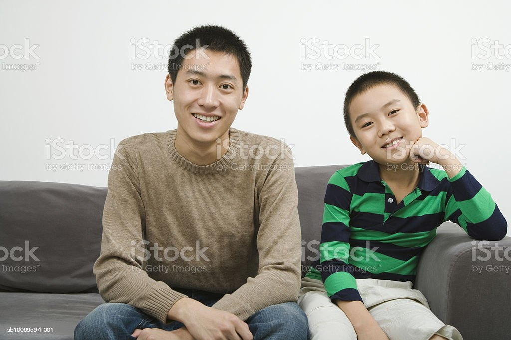 Young man sitting on couch with boy (8-9), smiling, portrait 免版稅 stock photo
