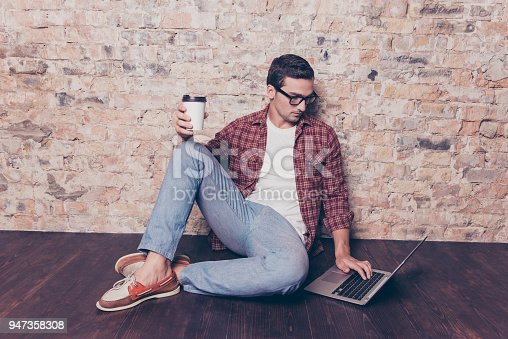 947303582 istock photo Young man sitting on floor with cup of coffee and laptop 947358308