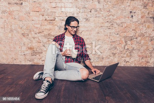 947303582 istock photo young man sitting on floor with laptop and drink coffee 951655454