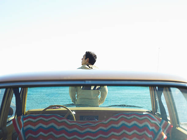 Young man sitting on hood of car beside sea, rear view stock photo