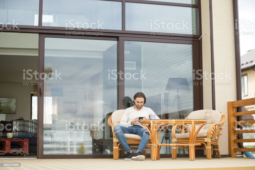 Young man sitting on house terrace chair, relaxing using phone stock photo