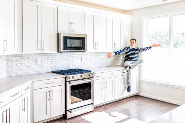 young man sitting on kitchen countertop with outstretched open arms in clean, modern, white home design - happy person buy appliances stock photos and pictures