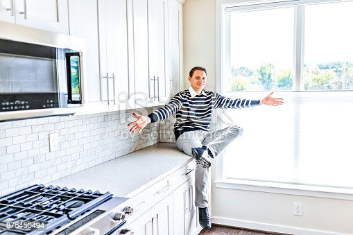 844050630 istock photo Young man sitting on kitchen countertop with outstretched open arms in clean, modern, white home design 875450494
