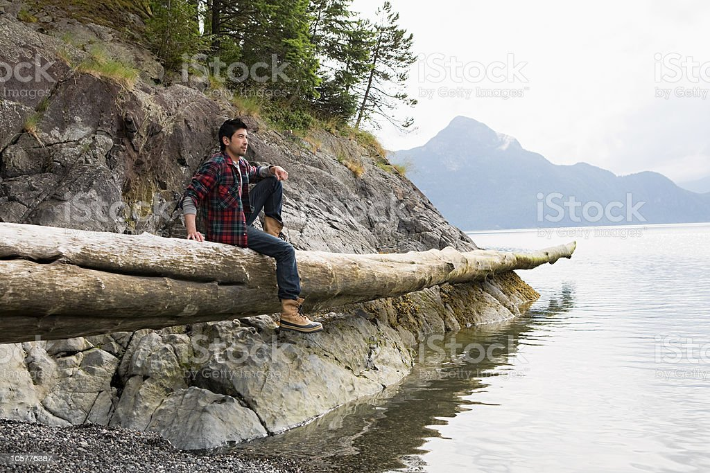 Young man sitting on log by lake royalty-free stock photo