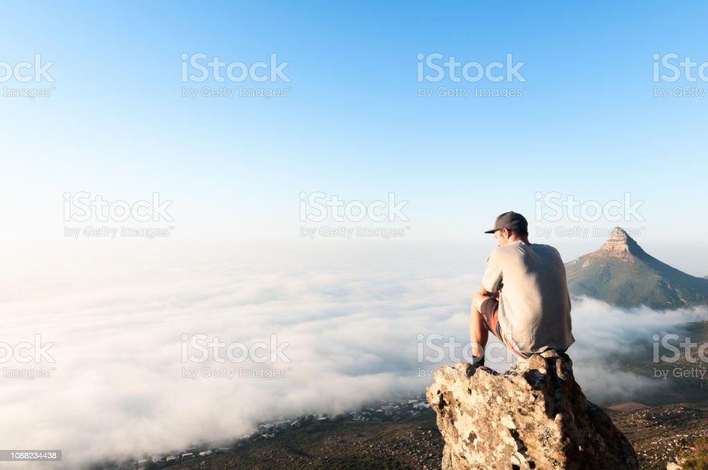 Junger Mann sitzt auf Berg über den Wolken von Cape Town, Südafrika – Foto