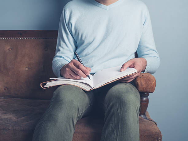 Young man sitting on old sofa writing stock photo