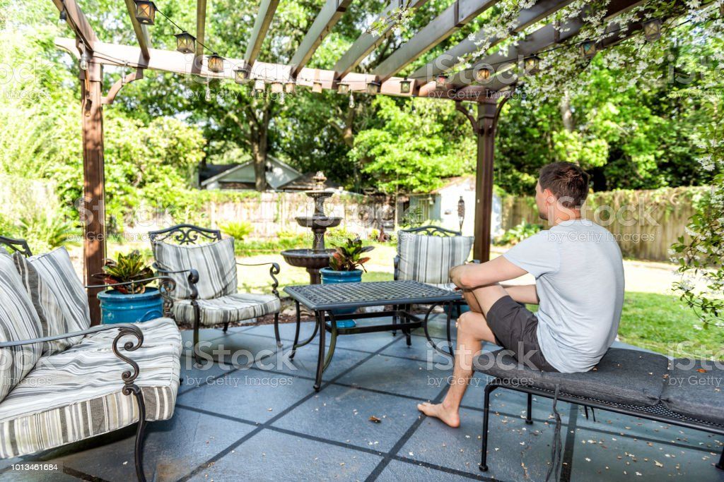 Swell Young Man Sitting On Patio Lounge Chair In Outdoor Spring Beatyapartments Chair Design Images Beatyapartmentscom
