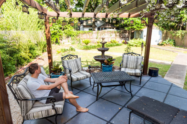 Young man sitting on patio lounge chair in outdoor spring flower garden in backyard of home zen with water fountain, pergola canopy gazebo, table, plants, sofa stock photo