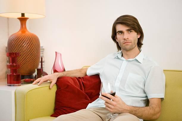 junger mann sitzt auf sofa holding wein glas - nachttischleuchte touch stock-fotos und bilder