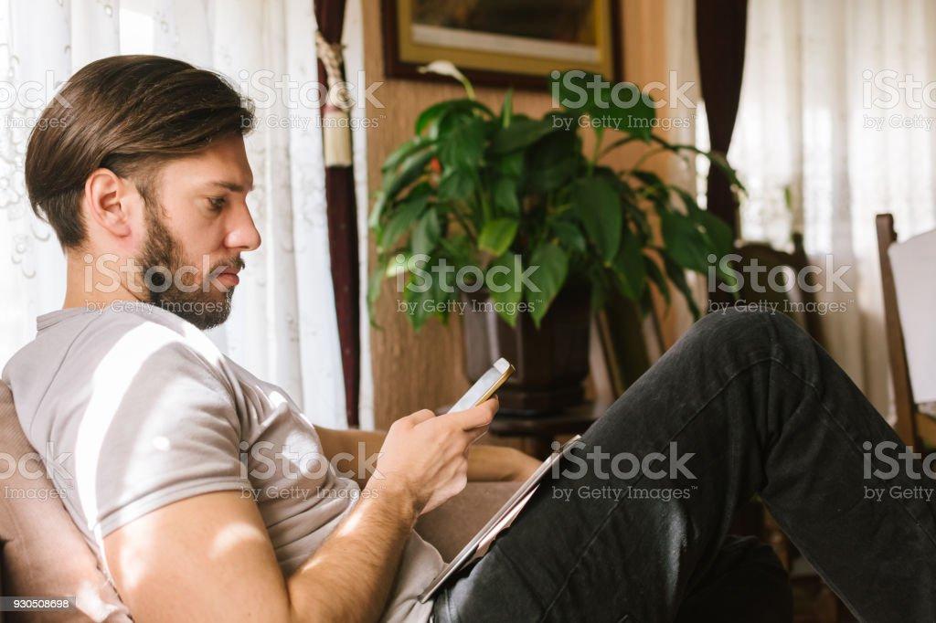 Hombre joven sentado en el sofá en la sala de estar y usar teléfono - foto de stock