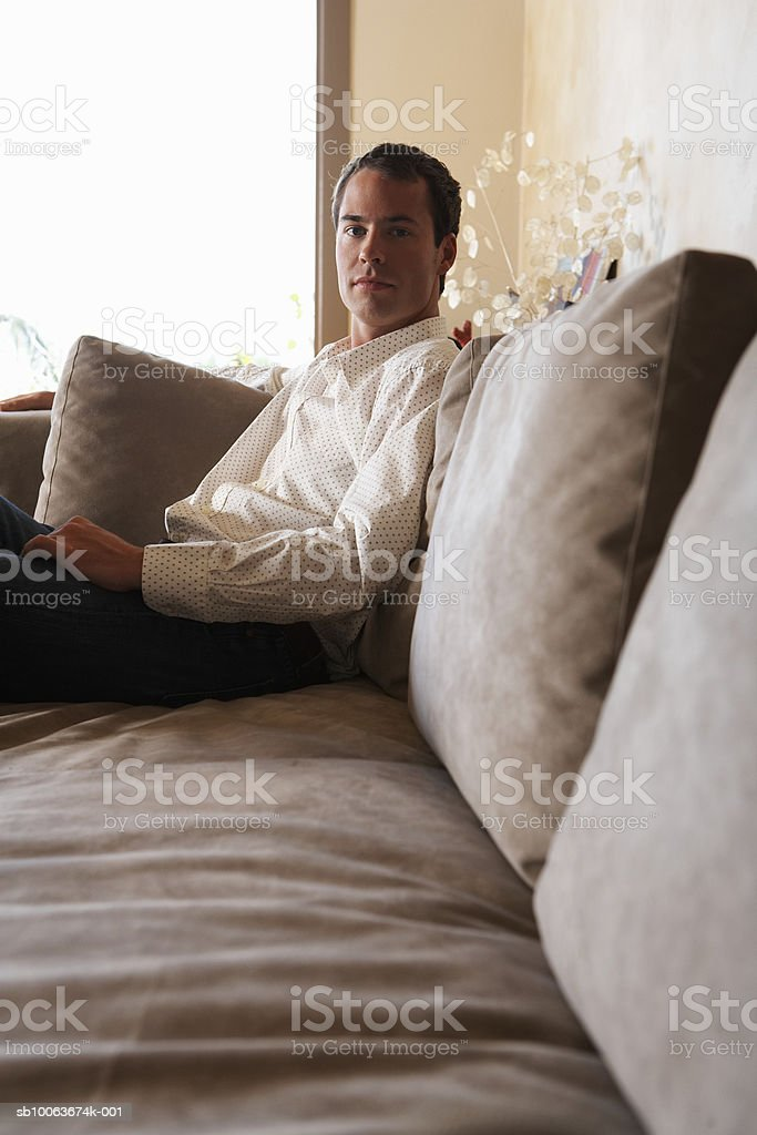 Young man sitting on sofa, portrait royalty free stockfoto