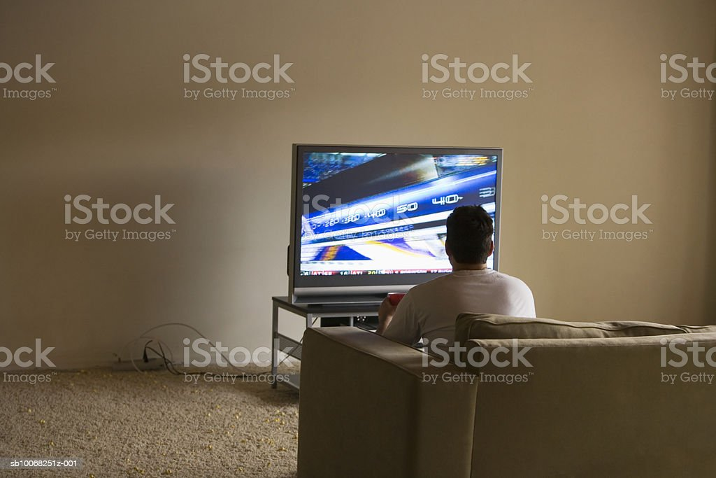Young man sitting on sofa watching tv, rear view 免版稅 stock photo