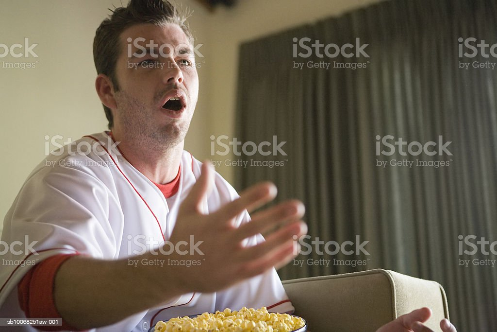 Young man sitting on sofa with popcorn on lap royalty free stockfoto