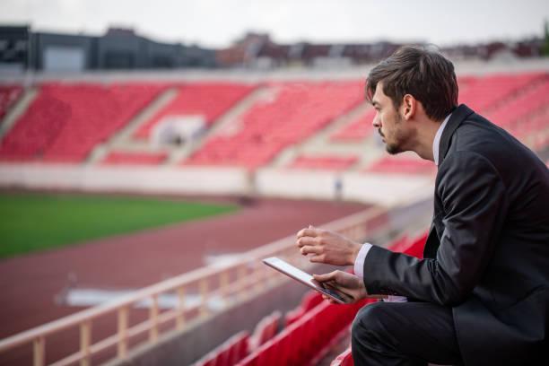 Jovem sentado na arquibancada do estádio - foto de acervo