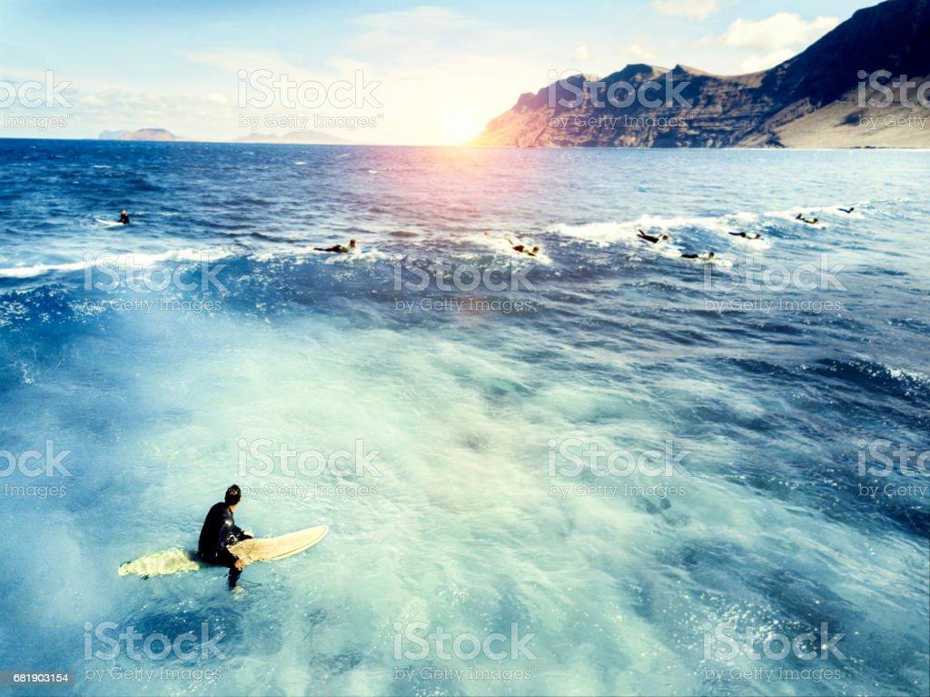 Young man sitting on surf board in sea stock photo