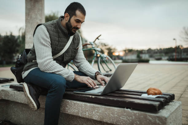 Young man sitting on the bench and using laptop in the public park stock photo