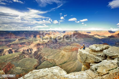 Young man sitting on a rock at the edge of the Grand Canyon.